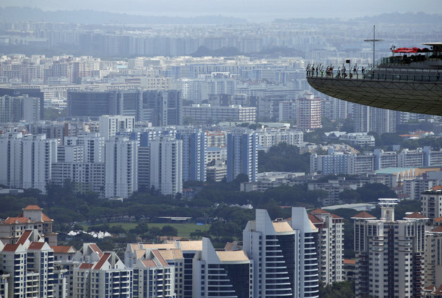 People look out from the observation tower of the Marina Bay Sands amongst public and private residential apartment buildings in Singapore, February 22, 2016. (Photo by Edgar Su/Reuters)