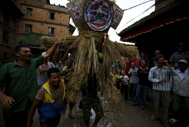 People carry an effigy of the demon Ghantakarna, before it is burnt to symbolize the destruction of evil, during the Ghantakarna festival at the ancient city of Bhaktapur, Nepal August 12, 2015. (Photo by Navesh Chitrakar/Reuters)