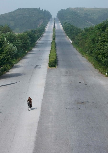 Yes, in North Korea, you can bike without danger on highways. Lot of peple try to stop cars but they need to wait for hours... When i asked to stop to take them as the tourist bus i had was empty, my guide refused, saying it was totally impossible to do this. (Photo by Eric Lafforgue/Exclusivepix Media)