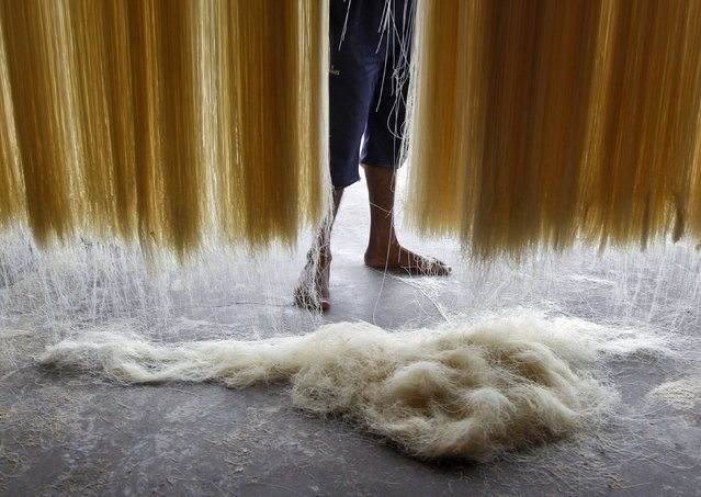 A worker hangs strands of vermicelli to dry inside a factory in the northern Indian city of Allahabad July 22, 2014. Vermicelli is a specialty eaten during the Muslim holy fasting month of Ramadan by many believers across the country. (Photo by Jitendra Prakash/Reuters)