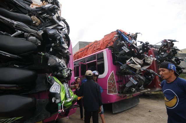 This photograph taken on June 21, 2017 shows racks of stacked motorcycles slung onto the rear end of buses in Palu, Indonesia's Central Sulawesi province, as Indonesians prepare for a mass exodus to their respective home towns ahead of the Eid ul-Fitr festival, which marks the end of the Muslim holy month of Ramadan, this weekend. (Photo by Opan Bustan/AFP Photo)