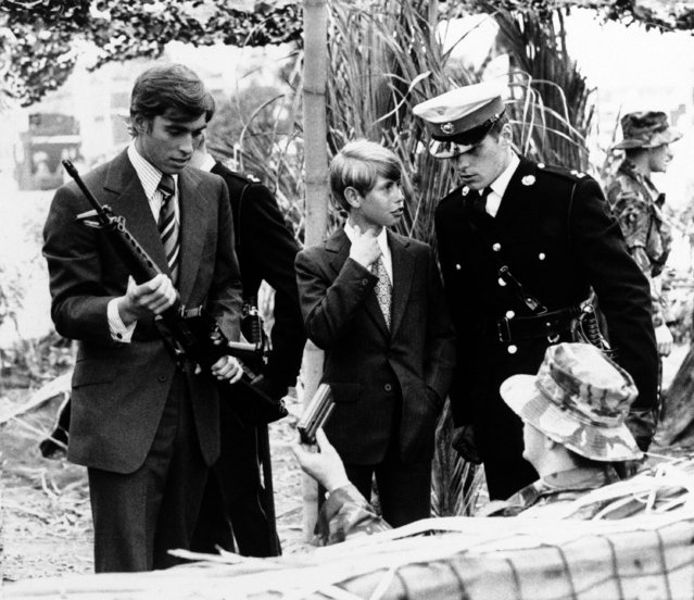 Britain's Prince Andrew, left, 17, check out an Armalite Rifle while his brother, Prince Edward, 13, talks with a royal marine officer in Plymouth, England on Friday, August 7, 1977. The brothers were visiting a display depicture life in the royal marines. (Photo by AP Photo)