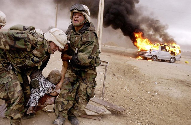 Lt. Jeffrey Goodman, left,  and Lance Cpl. Jorge Sanchez drag a wounded civilian away from his burning vehicle during an advance on Baghdad by the 2nd Tank Battalion