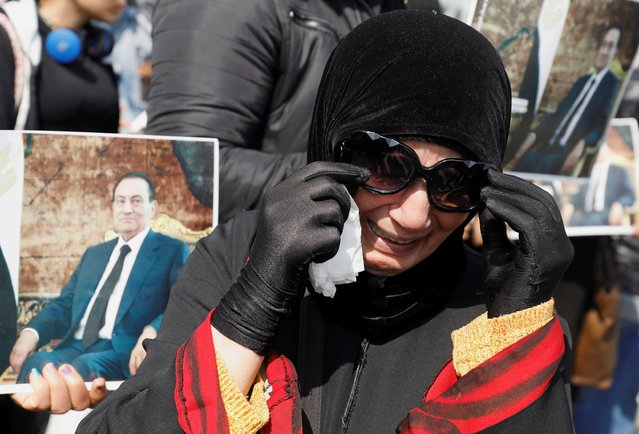 A supporter of former Egyptian President Hosni Mubarak reacts at a gathering near the main gate of a cemetery during his burial ceremony, east of Cairo, Egypt on February 26, 2020. (Photo by Mohamed Abd El Ghany/Reuters)