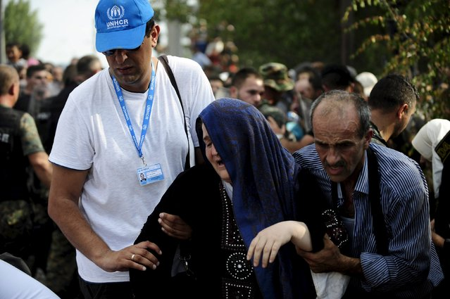 U.N. workers help a woman at the border line dividing Macedonia and Greece August 21, 2015. (Photo by Ognen Teofilovski/Reuters)