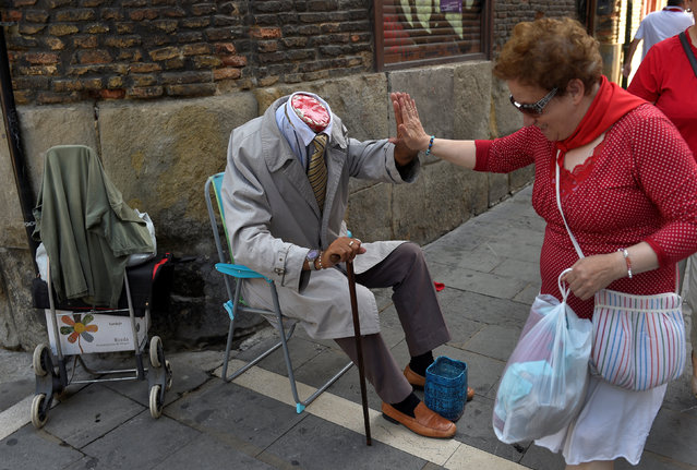 A woman greets a street artist at the San Fermin festival in Pamplona, northern Spain July 8, 2016. (Photo by Eloy Alonso/Reuters)