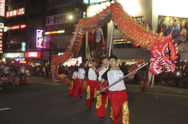 In this photo made late Saturday, August 9, 2014, in Keelung, Taiwan, a traditional Chinese dragon dance during a parade marking the beginning of the Chinese folklore's mid-summer's Ghost Month Festival. (Photo by Chiang Ying-ying/AP Photo)