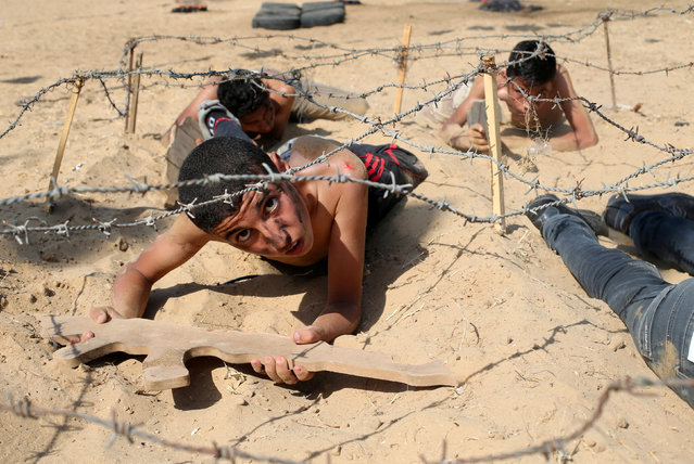 Young Palestinians crawl under barbed wire during a military-style exercise at a summer camp organised by the Islamic Jihad Movement in Khan Younis in the southern Gaza Strip July 13, 2016. (Photo by Ibraheem Abu Mustafa/Reuters)