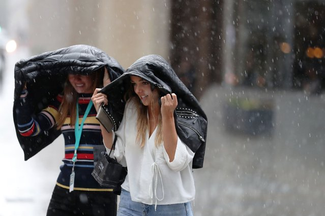 Pedestrians dash through the streets of central London during a downpour on August 10, 2018. (Photo by Daniel Leal-Olivas/AFP Photo)