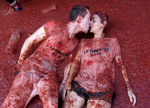 """Revelers kiss each other while lying in tomato pulp after the annual """"Tomatina"""" (tomato fight) in Bunol, near Valencia, Spain, August 26, 2015. (Photo by Heino Kalis/Reuters)"""