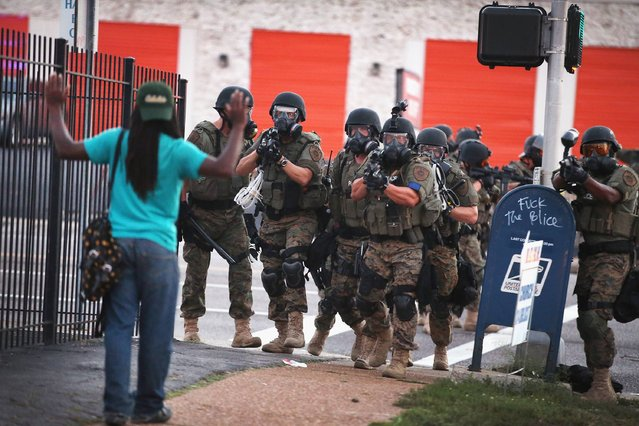 Police force protestors from the business district into nearby neighborhoods on August 11, 2014 in Ferguson, Missouri. Police responded with tear gas and rubber bullets as residents and their supporters protested the shooting by police of an unarmed black teenager named Michael Brown who was killed Saturday in this suburban St. Louis community. (Photo by Scott Olson/Getty Images)