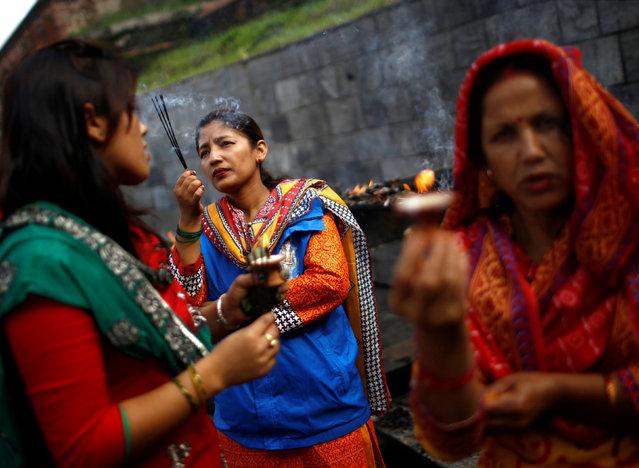 Devotees offer prayers at Pashupatinath temple to mark the Shrawan Sombar festival in Kathmandu, Nepal, July 18, 2016. (Photo by Navesh Chitrakar/Reuters)