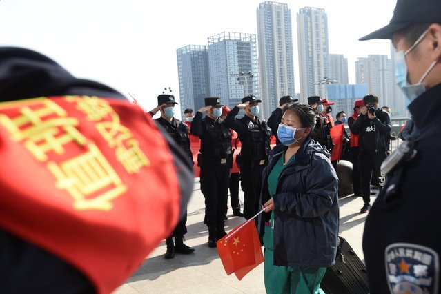 Police officers salute as a medical worker from outside Wuhan arrives at the Wuhan Railway Station before leaving the epicenter of the coronavirus outbreak, in Hubei province, China, March 17, 2020. (Photo by Reuters/China Stringer Network)