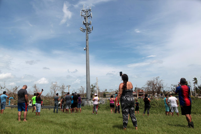 People stop on a highway near a mobile phone antenna tower to check for mobile phone signal, after the area was hit by Hurricane Maria, in Dorado, Puerto Rico September 22, 2017. (Photo by Alvin Baez/Reuters)