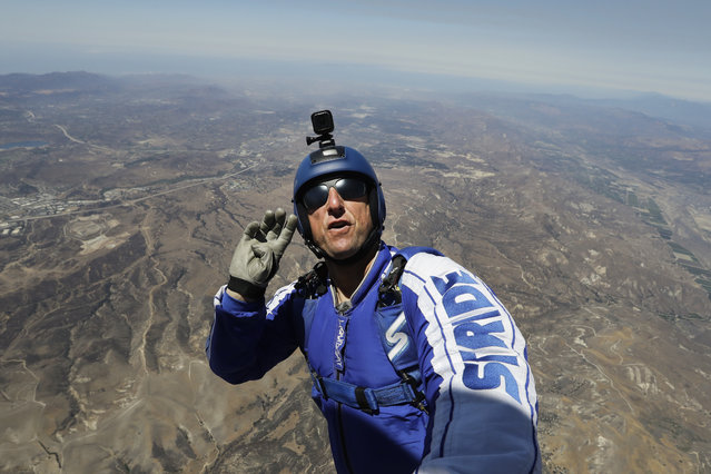 In this Monday, July 25, 2016 photo, skydiver Luke Aikins signals to pilot Aaron Fitzgerald as he prepares to jump from a helicopter in Simi Valley, Calif. (Photo by Jae C. Hong/AP Photo)