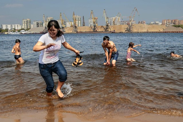 People cool themselves off on the banks of the Moskva river in Moscow, Russia, on August 12, 2014. (Photo by Ivan Sekretarev/Associated Press)