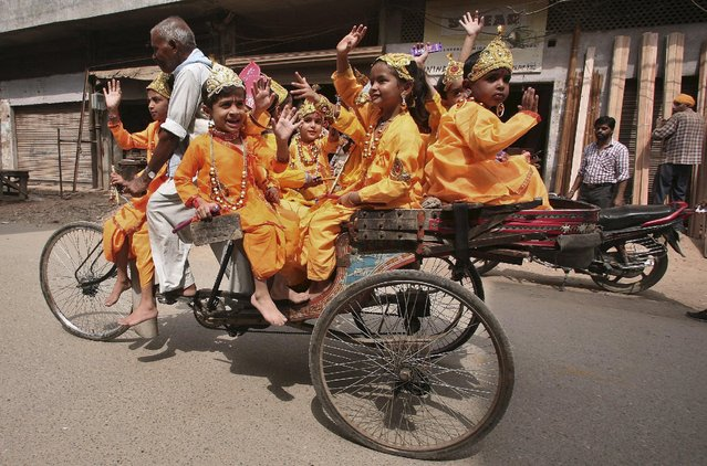 Children dressed as the Hindu Lord Krishna ride on a cycle rickshaw as they travel to their school to attend a function on the eve of the Janmashtami festival in Amritsar, India, September 4, 2015. (Photo by Munish Sharma/Reuters)