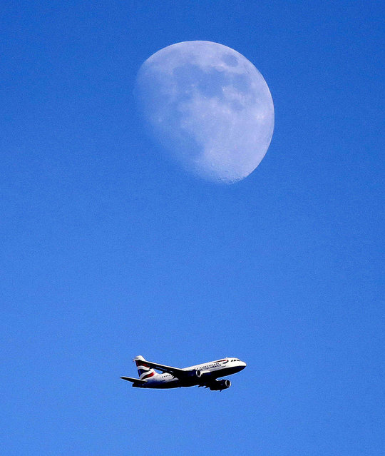 A British Airways plane approches landing at Heathrow Airport below the moon in London, Tuesday, July 4, 2017. (Photo by Frank Augstein/AP Photo)