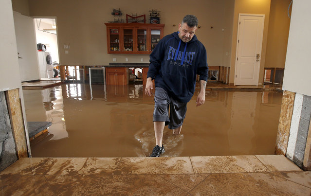 A dismayed Nick Kriaris wades through his flooded home after heavy rains caused severe flash flooding Monday, September 8, 2014, in Phoenix. His home has flooded three times in the past month, and he had just fixing the damage in his home from the previous two monsoon storm floodings when the storm hit. The Monday morning storm set an all-time record for rainfall in Phoenix in a single day. (Photo by Ross D. Franklin/AP Photo)