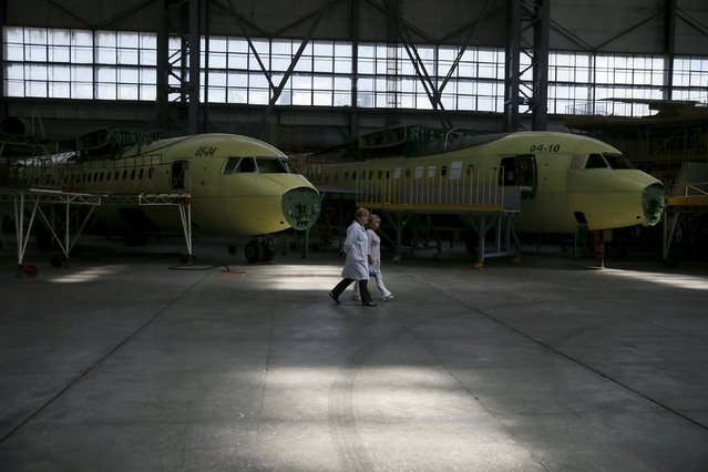 Staff pass by near new Antonov airplanes at the Antonov aircraft plant in Kiev, Ukraine, September 7, 2015. (Photo by Gleb Garanich/Reuters)