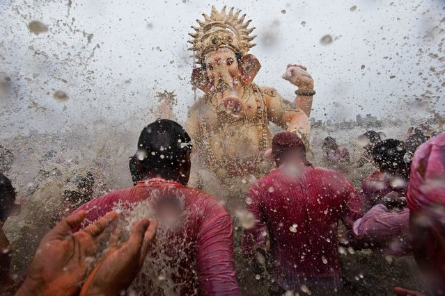 Devotees splash water on an idol of Hindu elephant god Ganesh, the deity of prosperity, as it is carried for immersion into the Arabian Sea on the last day of the Ganesh Chaturthi festival in Mumbai September 8, 2014. Ganesh idols are taken through the streets in a procession accompanied by dancing and singing, and later immersed in a river or the sea, symbolising a ritual seeing-off of his journey towards his abode, taking away with him the misfortunes of all mankind. (Photo by Bernat Armangue/AP Photo)