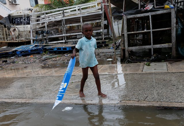 A girl walks through flooded streets, after Hurricane Earl hits, in Belize City, Belize August 4, 2016. (Photo by Henry Romero/Reuters)