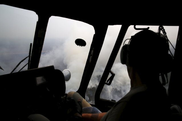 An Mi-17 helicopter pilot flies over a burning forest at Ogan Komering Ulu area in Indonesia's south Sumatra province September 10, 2015. (Photo by Reuters/Beawiharta)