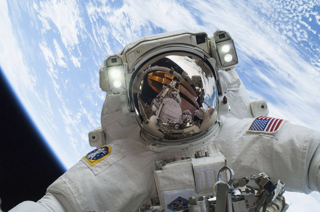 Astronaut Mike Hopkins as he participates in the second of two spacewalks which took place on December 24, 2013. (Photo by Reuters/NASA)
