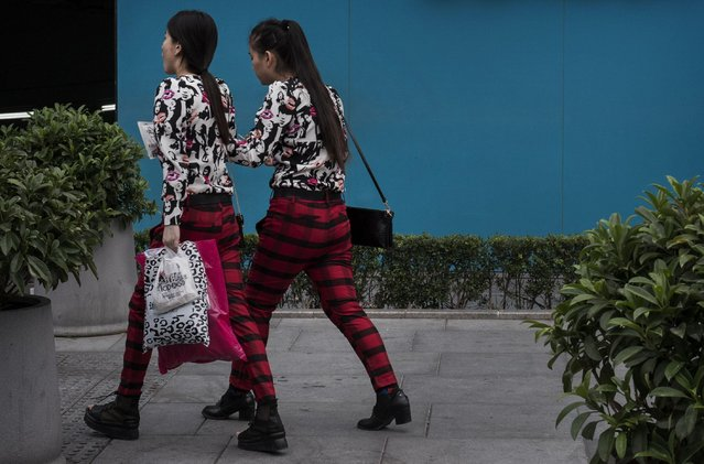 Chinese women wear identical clothes as they shop together at an outdoor mall on September 12, 2014 in Beijing, China. (Photo by Kevin Frayer/Getty Images)