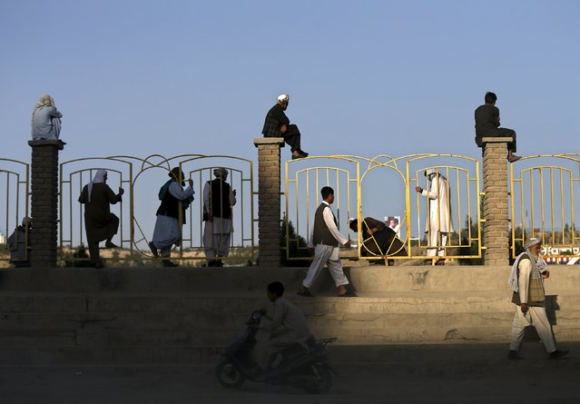 Afghan men sit on a wall as they watch others play football in Kabul, Afghanistan September 11, 2015. (Photo by Mohammad Ismail/Reuters)