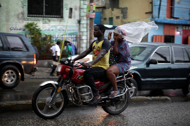 A woman covers herself with a piece of plastic as she rides on a motorbike in Port-au-Prince, Haiti, August 10, 2016. (Photo by Andres Martinez Casares/Reuters)