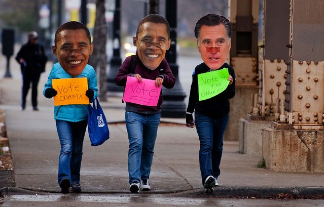 Three Obama supporters walk around the south side of Chicago, IL, November 6, 2012 wearing Obama and Romney masks holding placards asking people to vote. Citizens around the United States head to the polls to vote on the country's next president including in Ohio, a state with 18 electoral votes, were the race between US President Barack Obama and Mitt Romney is very close.  (Photo by  Jim Watson/AFP Photo)