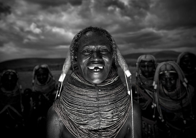 """Playing with light in Mwila tribe – Angola. Funny time when i started to play with the flash! Mumuhuila women are serious drinkers, and sometimes, they even drink more than the men! Some can in the camp at 7 in the morning to have a look at the wine bottles..and finished them!"". (Eric Lafforgue)"