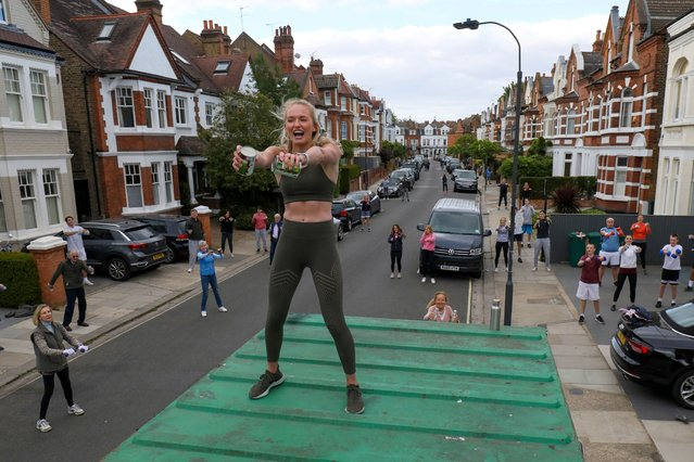 Personal trainer Flo Dowler leads the residents of Napier Avenue in a workout fitness class in Fulham, West London, Britain on May 11, 2020. (Photo by Kevin Coombs/Reuters)