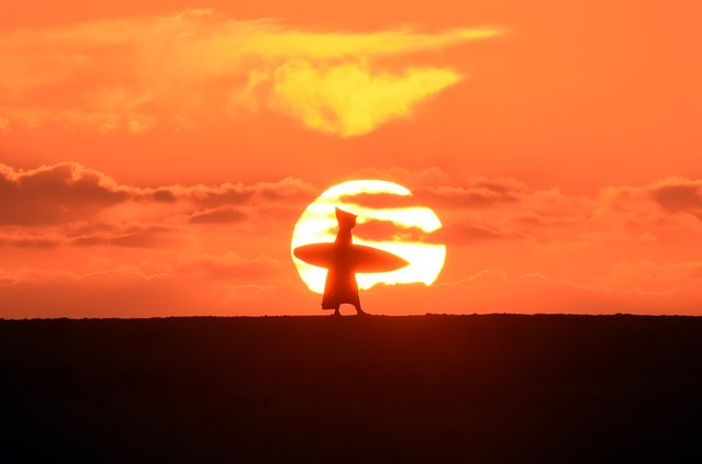 A Moroccan surfer walks along the beach as the sun sets in Oued Charrat 30 kilometres from the capital Rabat on October 7, 2014. (Photo by Fadel Senna/AFP Photo)