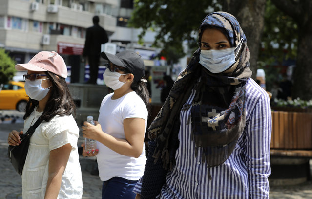 A woman and children wearing face masks to protect against coronavirus, walk in a public garden, in Ankara, Turkey, Friday, June 12, 2020. Turkey's President Recep Tayyip Erdogan revealed on Tuesday new plans to ease restrictions in place to curb the spread of the coronavirus, including the July 1 reopening of theaters, cinemas and other entertainment centers. (Photo by Burhan Ozbilici/AP Photo)