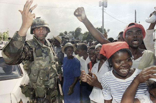A U.S. soldier tries to calm an overzealous crowd at the port in Port-au-Prince, Thursday, September 22, 1994 as a Haitian police car passes by. The port has been secured by the U.S. military since moving into Haiti on Monday. The United States muscled toward total military control of Haiti on Thursday, breaking up the army's heavy weapons, guarding pro-democracy activists and giving U.S. troops more leeway to use force. (Photo by Rick Bowmer/AP Photo)