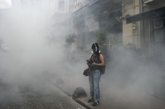 A journalist stands in tear gas  demonstrators gathered for a rally staged by the LGBT community on Istiklal avenue in Istanbul on June 26, 2016. Riot police fired tear gas and rubber bullets to disperse protesters defying a ban on the city's Gay Pride parade. Authorities in Turkey's biggest city had banned the annual parade earlier this month citing security reasons, sparking anger from gay rights activists. (Photo by Ozan Kose/AFP Photo)