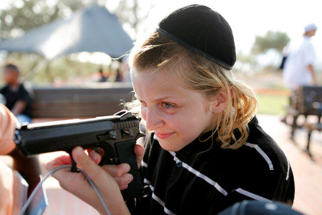 "A boy plays with a gun during an ""open day"", exhibiting various policing skills and equipment to the public, in the southern Israeli city of Ashdod, August 29, 2016. (Photo by Amir Cohen/Reuters)"