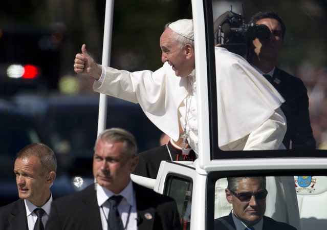 Pope Francis give the thumbs-up from the popemobile during a parade around the Ellipse near the White House in Washington, Wednesday, September 23, 2015. (Photo by Carolyn Kaster/AP Photo)