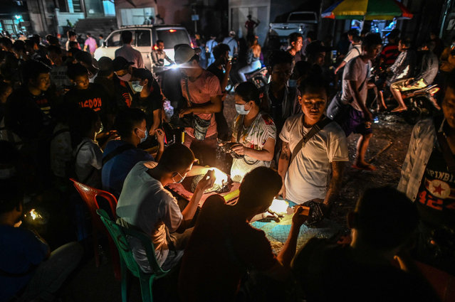 This photo taken on July 5, 2020 shows miners offering jade for sale to brokers in a jade night market in Hpakant in Kachin state. Myanmar is one of the world's biggest sources of jadeite and the industry is supercharged by demand for the green gem from neighbouring China. The landslide on July 2, in which more than 170 miners were killed, was the worst accident in memory to befall Myanmar's notoriously dangerous jade mines. (Photo by Ye Aung Thu/AFP Photo)