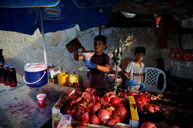Boys prepare freshly squeezed pomegranate juice which they sell on the street in the Israeli Arab city of Umm al-Fahm August 16, 2016. (Photo by Ammar Awad/Reuters)