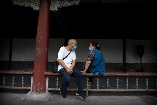 People wearing face masks to protect against the coronavirus sit on a railing at the Temple of Heaven in Beijing, Saturday, July 18, 2020. Authorities in a city in far western China have reduced subways, buses and taxis and closed off some residential communities amid a new coronavirus outbreak, according to Chinese media reports. They also placed restrictions on people leaving the city, including a suspension of subway service to the airport. (Photo by Mark Schiefelbein/AP Photo)