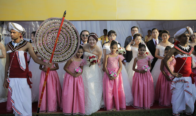 A Chinese bride poses for a photograph with a Sri Lankan flower girl during a mass wedding ceremony in Colombo, Sri Lanka, Sunday, December 17, 2017. Fifty Chinese couples were married at a mass ceremony in Sri Lanka's capital to mark the 60th anniversary of diplomatic relations between the two countries and to promote the island nation as a tourist destination. (Photo by Eranga Jayawardena/AP Photo)