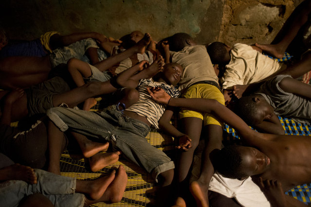 In this September 24, 2013 photo, Quranic students known as talibes sleep together in the crowded room that serves as their classroom and living quarters, at a daara, or Quranic school, in the Medina Gounass suburb of Dakar, Senegal. (Photo by Rebecca Blackwell/AP Photo)
