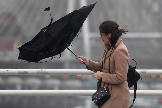 A woman holds an umbrella, blown inside-out by the wind, as she walks across Waterloo Bridge in London on January 14, 2020. Weather warnings issued yesterday by Britain's Met Office remained in force Tuesday after Storm Brendan brought winds of nearly 90mph to parts of the country