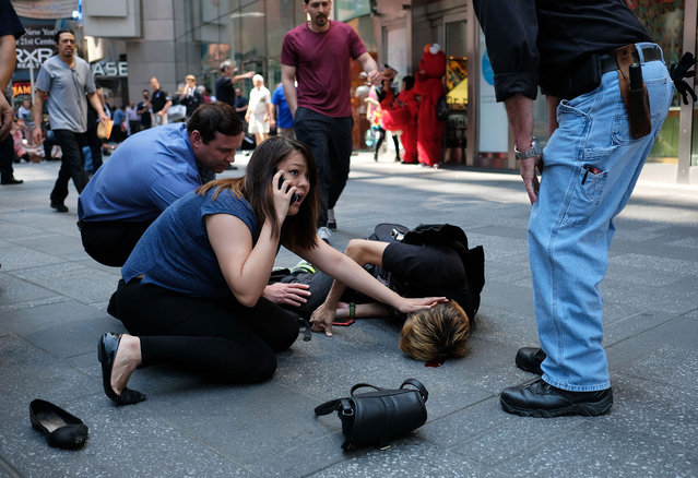 People attend to an injured man after a car plunged into him in Times Square in New York on May 18, 2017. A car plowed into a crowd of pedestrians in New York's bustling Times Square, leaving one person dead and at least 12 other injured. (Photo by Jewel Samad/AFP Photo)