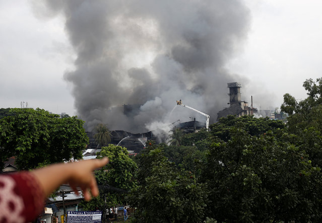 A woman points to a garment packaging factory on fire outside of Dhaka, Bangladesh, September 10, 2016. At least fifteen people have been killed and 70 injured, many critically, in a huge fire triggered by a boiler explosion at a Bangladeshi packaging factory, officials said on September 10. (Photo by Mohammad Ponir Hossain/Reuters)