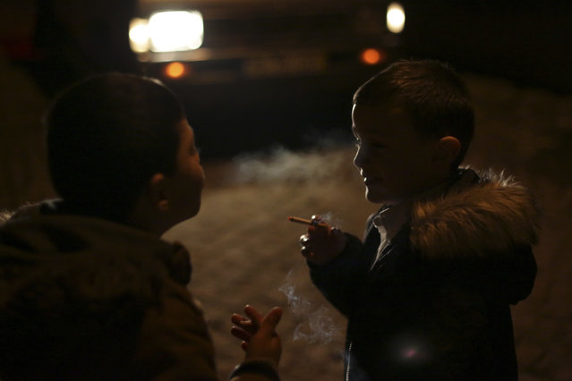 A young boy blows cigarette smoke on his friend's face in the village of Vale de Salgueiro, northern Portugal, during the local Kings' Feast Friday, January 5, 2018. (Photo by Armando Franca/AP Photo)