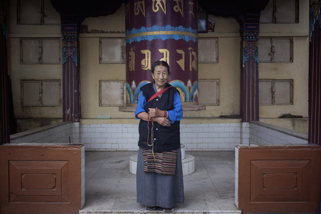 In this Thursday, September 25, 2014 photo, Sonam Dolma, 75, poses for a photo near a prayer wheel in Dharamsala, India. Dolma escaped from Tibet in 1959 and made Dharmsala her home. She says she wishes to visit Tibet someday. (Photo by Tsering Topgyal/AP Photo)